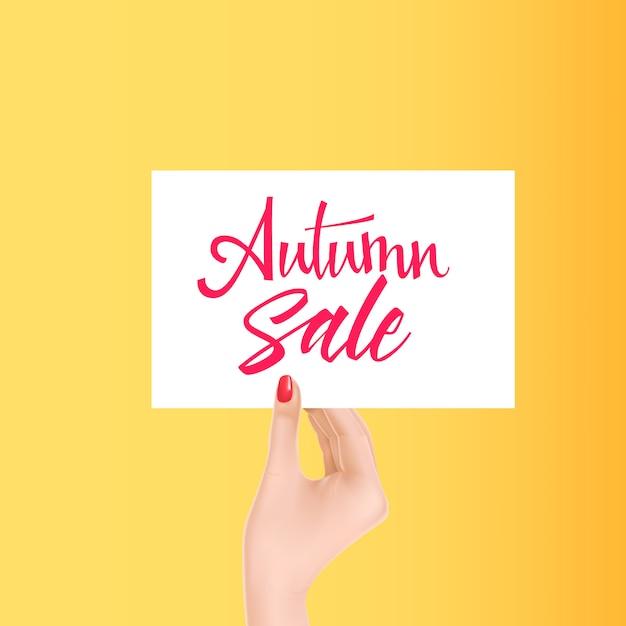 Mão segurando o cartão branco com letras de venda outono Vetor grátis