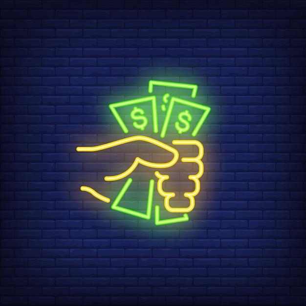 Mão segurando o sinal de néon de notas de dólar Vetor grátis