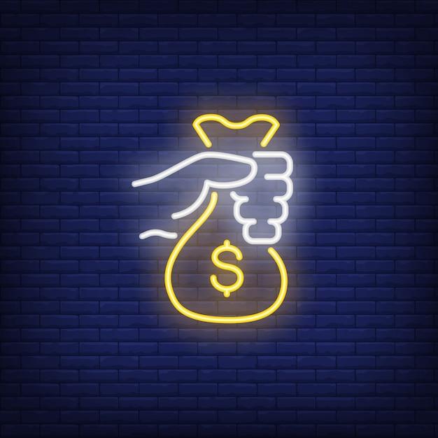Mão segurando o sinal de néon de saco de dinheiro Vetor grátis