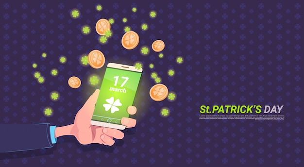 Mão segurando o telefone inteligente com folha de trevo e moedas de ouro sobre fundo de dia feliz st patricks Vetor Premium
