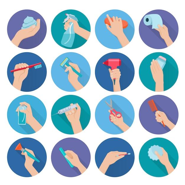 Mão segurando objetos de higiene pessoal plano conjunto de ícones Vetor grátis