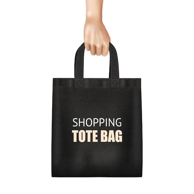 Mão segurando sacola de compras de lona preta elegante Vetor grátis