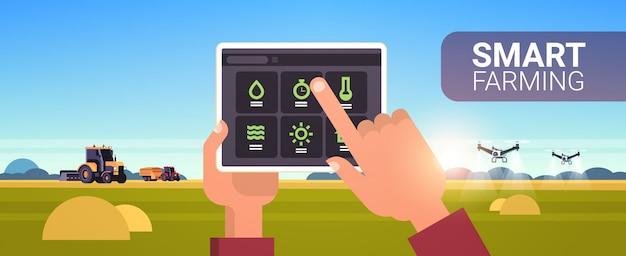 Mãos de fazendeiro usando tablet controlando trator e pulverizador de zangão no campo agricultura inteligente tecnologia moderna organização de colheita aplicação conceito paisagem cópia espaço Vetor Premium
