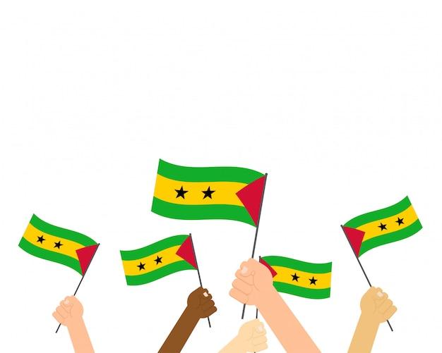 Mãos segurando bandeiras de são tomé e príncipe Vetor Premium