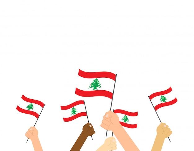 Mãos segurando bandeiras do líbano Vetor Premium
