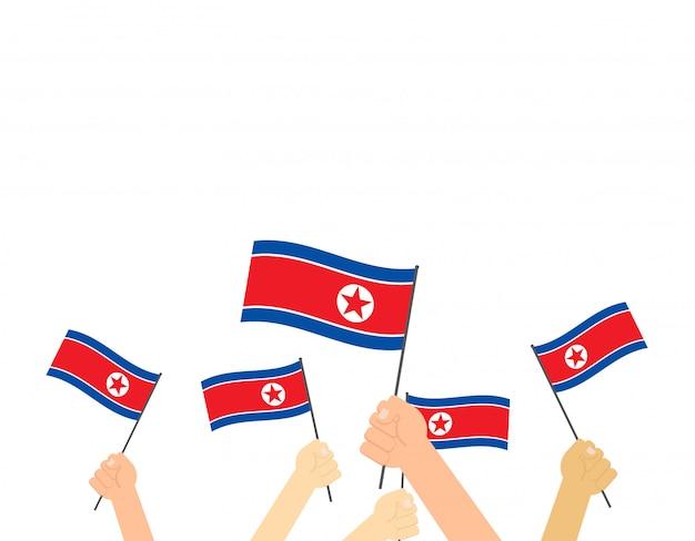 Mãos, segurando, coréia norte, bandeiras Vetor Premium
