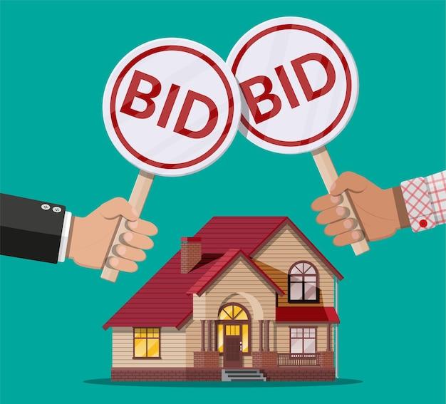 Mãos segurando uma raquete de leilão. placa de oferta. imobiliário, construção de casas. Vetor Premium