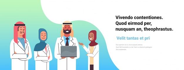 Médico árabe segurar banner on-line de computador portátil Vetor Premium