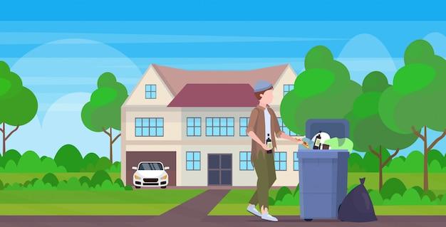 Mendigo homem segurando garrafa de álcool vagabundo procurando comida e roupas na lata de lixo na rua desempregados desempregados desemprego pobreza cottage conceito edifício campo fundo comprimento total Vetor Premium