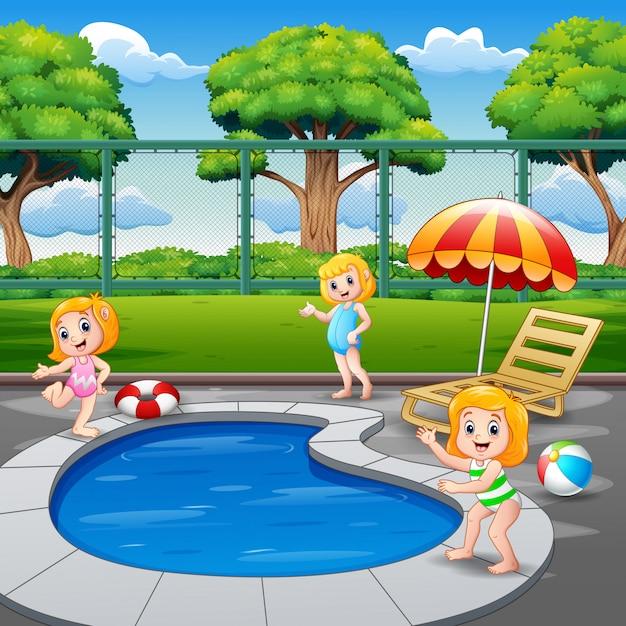 Meninas felizes que jogam na piscina Vetor Premium