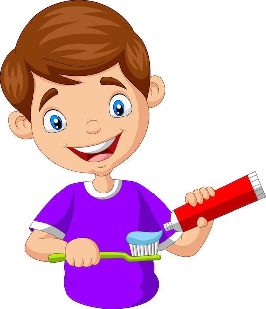 Menino bonitinho apertando creme dental em uma escova de dentes Vetor Premium