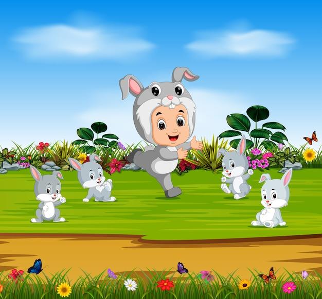Menino bonito vestindo traje coelho e brincar com coelhos Vetor Premium