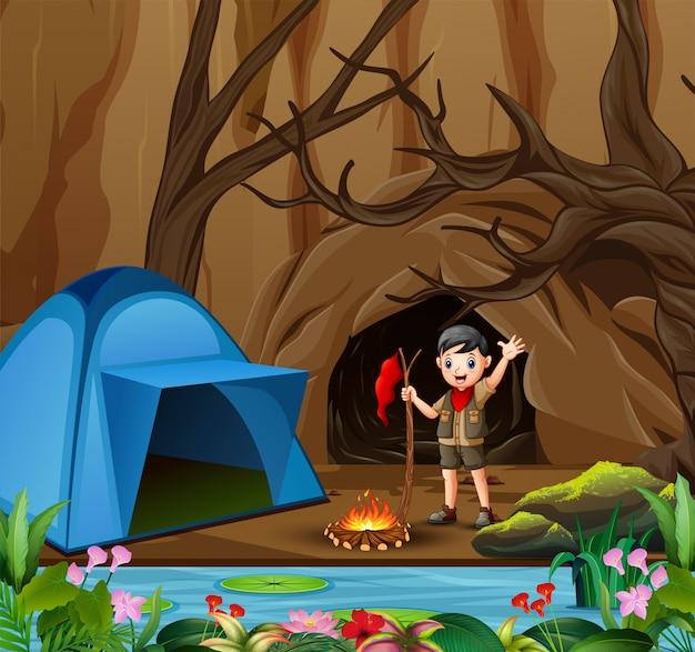 Menino de escoteiro no fundo de floresta de verão ao ar livre com tenda Vetor Premium