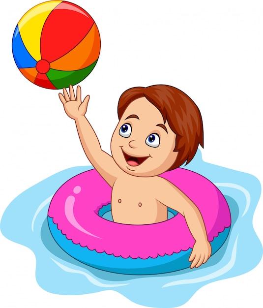 Menino dos desenhos animados que joga o círculo inflável com uma bola de praia Vetor Premium