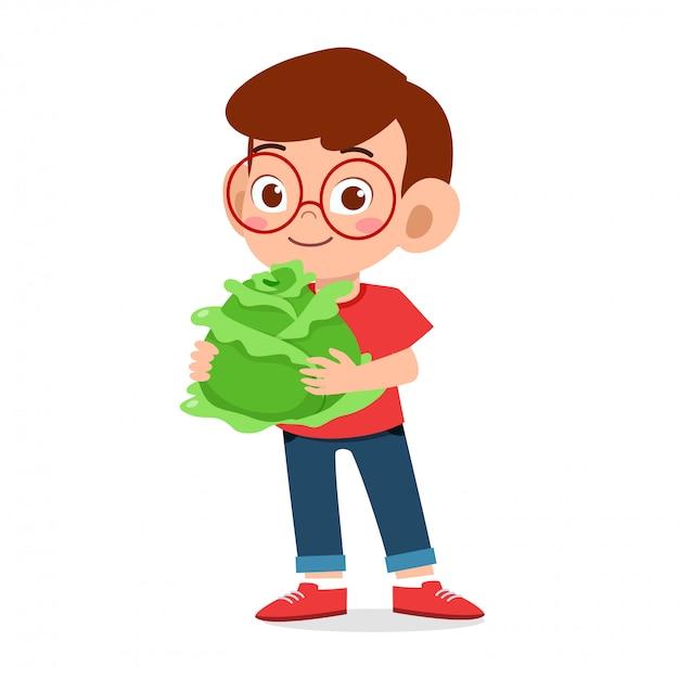 Menino feliz criança fofa segurando legumes frescos Vetor Premium