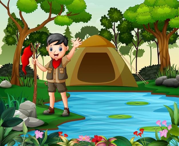 Menino feliz escoteiro acampar na natureza Vetor Premium