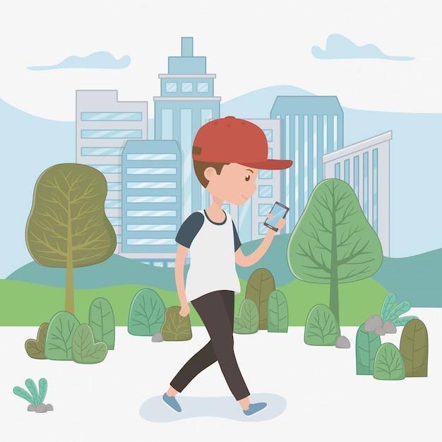 Menino jovem, andar, usando, smartphone, parque Vetor grátis