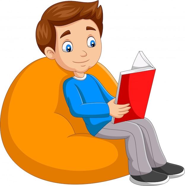Menino lendo um livro sentado no travesseiro grande Vetor Premium