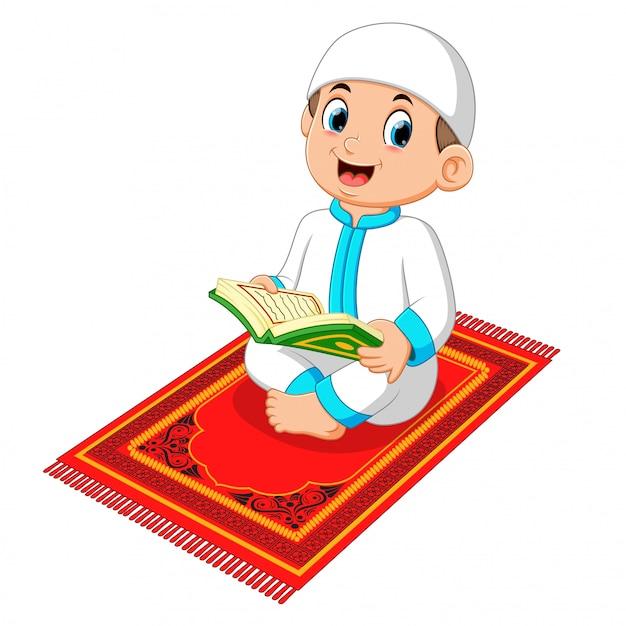 Menino muçulmano lendo o alcorão sagrado Vetor Premium