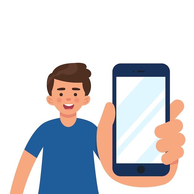 Menino no modo casual, mostrando a tela do smartphone Vetor Premium