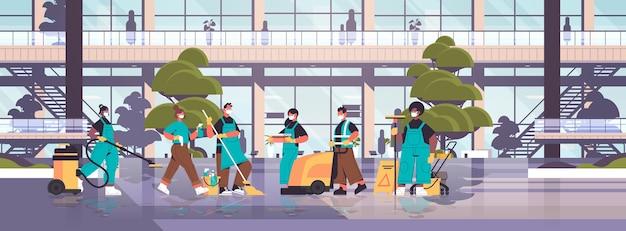 Misture limpador de raça em máscaras desinfetando células de coronavírus para evitar covid-19 pandemia de limpeza serviço conceito de desinfecção hospital edifício exterior horizontal Vetor Premium