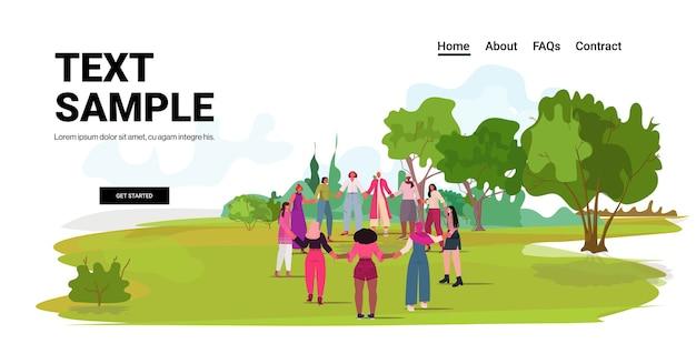Mix raça meninas de mãos dadas juntas em pé movimento de empoderamento feminino mulheres conceito de poder parque urbano paisagem fundo cópia espaço Vetor Premium