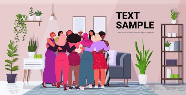 Mix raça meninas se abraçando em pé juntas movimento de empoderamento feminino conceito de poder feminino sala de estar interior cópia espaço Vetor Premium