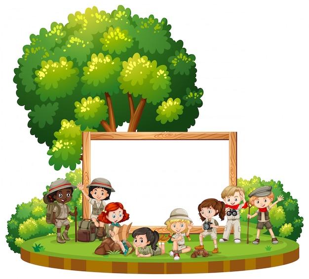 Modelo de sinal em branco com crianças em roupa ao ar livre Vetor grátis