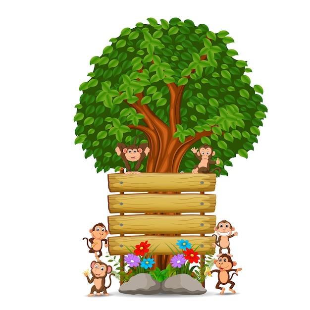 Muitos macaco na frente de uma tabuleta de madeira vazia Vetor Premium