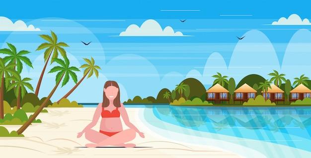 Mulher com sobrepeso no maiô mais garota de tamanho na praia sentado pose de lótus obesidade conceito de férias de verão tropical ilha seascape fundo comprimento total plana horizontal Vetor Premium