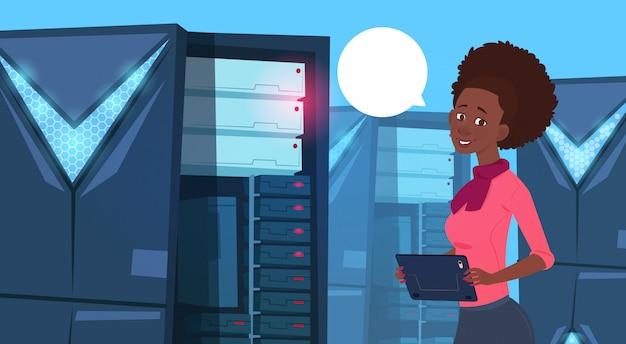 Mulher de negócios americano africano trabalhando em tablet digital no centro de banco de dados moderno ou sala de servidor b Vetor Premium