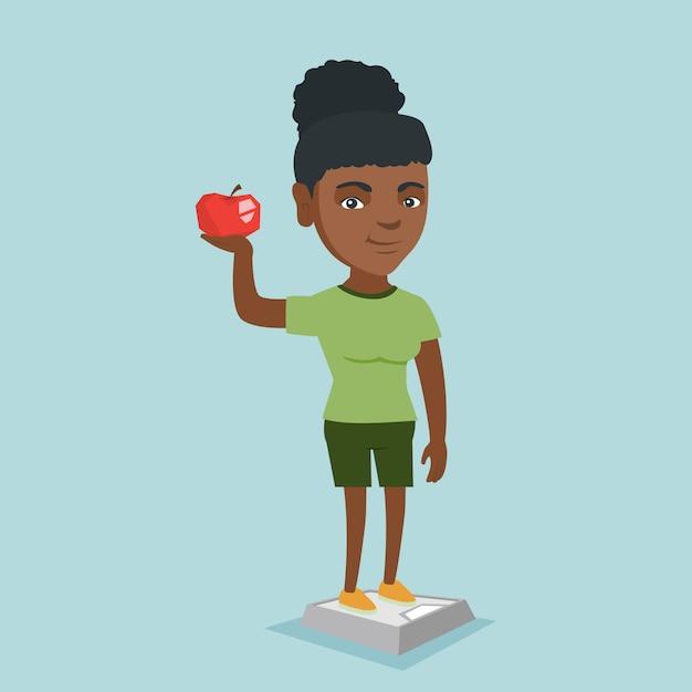 Mulher em pé na balança e segurando a maçã na mão. Vetor Premium