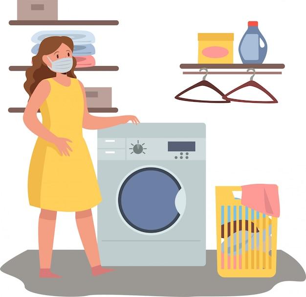 Mulher está lavando roupa em casa enquanto estiver usando máscara médica Vetor Premium