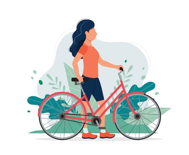 Mulher feliz com uma bicicleta no parque. Vetor Premium