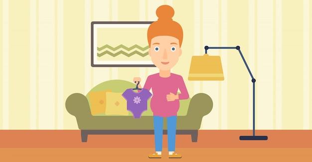 Mulher grávida com roupas para o bebê. Vetor Premium