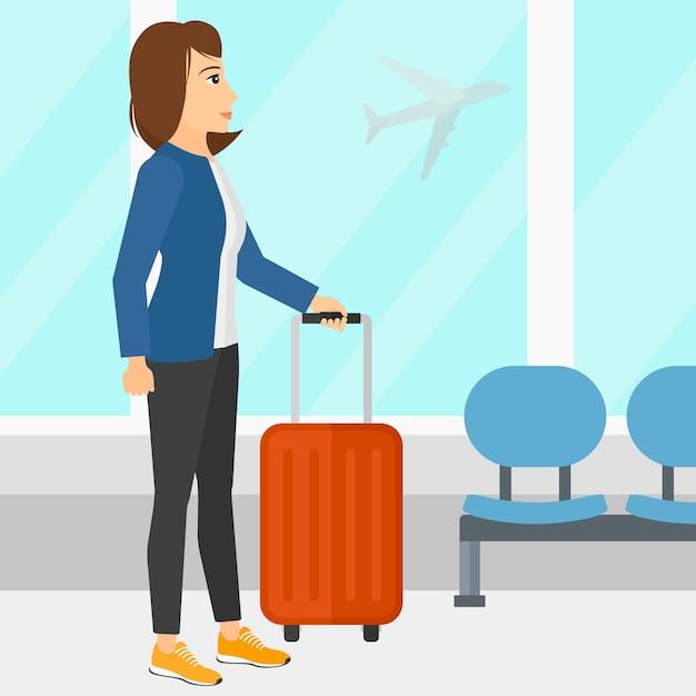 Mulher no aeroporto com mala Vetor Premium