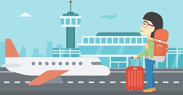 Mulher no aeroporto com mala. Vetor Premium