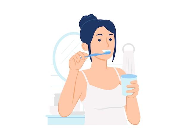 Mulher no banheiro escovando os dentes e segurando um copo de água ilustração do conceito Vetor Premium