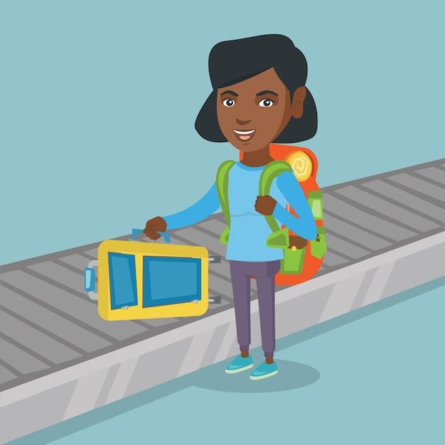 Mulher pegando a mala da correia transportadora. Vetor Premium