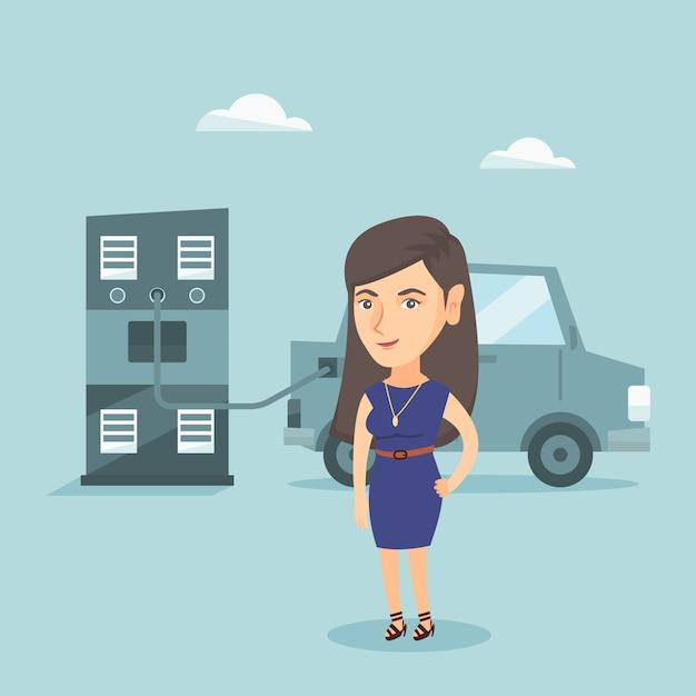Mulher que carrega o carro bonde na estação de carregamento. Vetor Premium