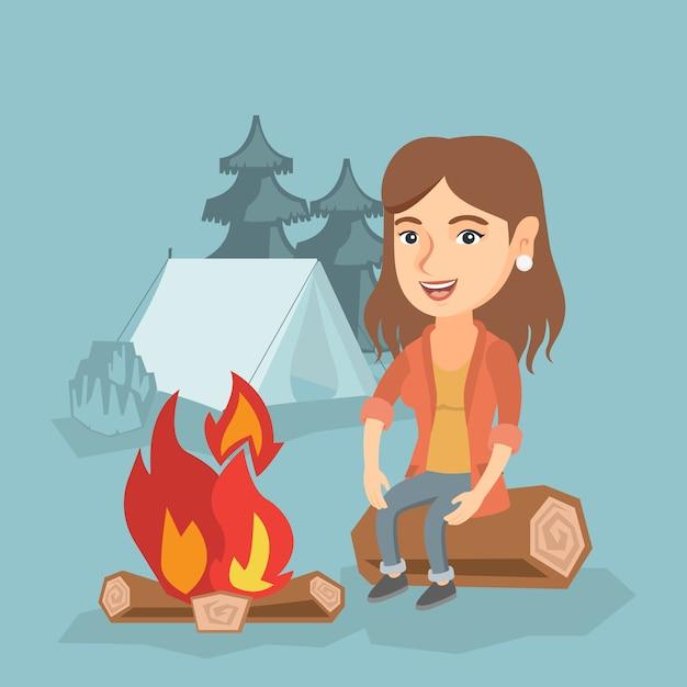 Mulher que senta-se no log perto da fogueira no acampamento. Vetor Premium