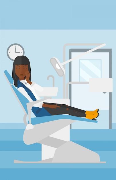 Mulher que sofre na cadeira odontológica. Vetor Premium