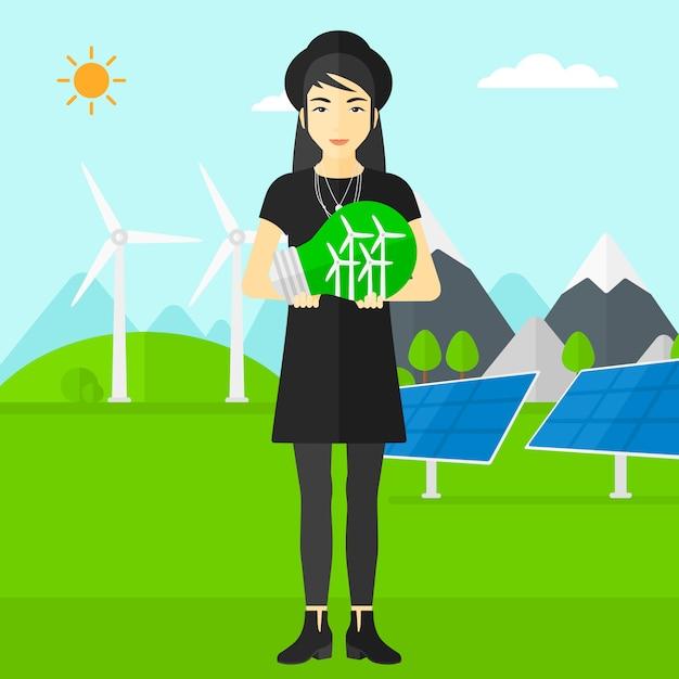Mulher segurando a lâmpada com moinhos de vento dentro Vetor Premium