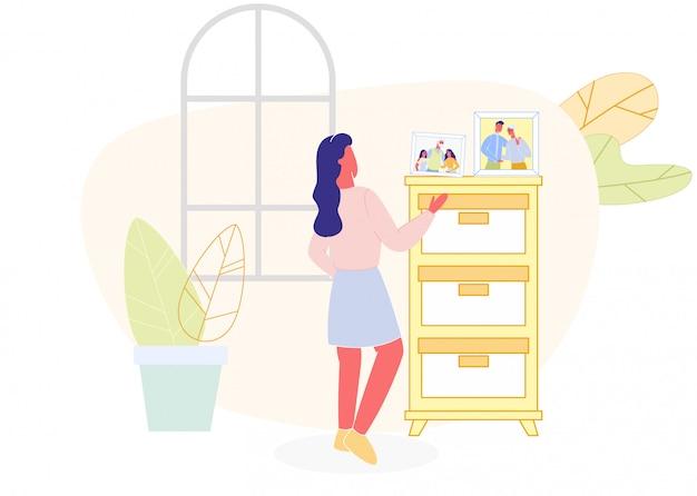 Mulher vendo foto de família na cômoda, sala de estar Vetor Premium