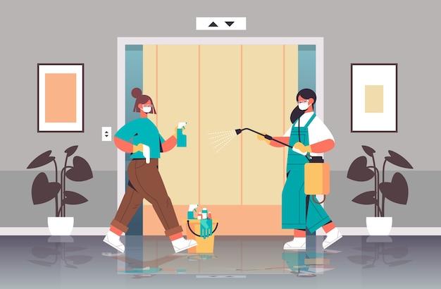 Mulheres de limpeza em máscaras desinfetando células de coronavírus em elevador para prevenir covid-19 pandemia de limpeza serviço de desinfecção controle de epidemia Vetor Premium