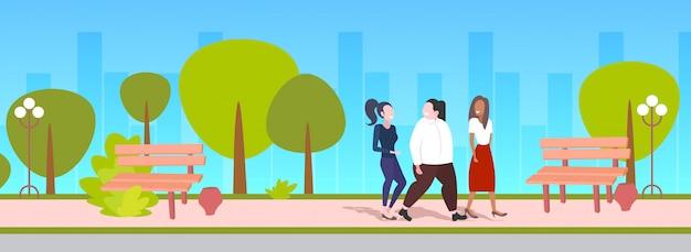 Mulheres discutindo durante andar meninas de raça ao ar livre tendo discussão amizade obesidade conceito urbano parque cityscape Vetor Premium