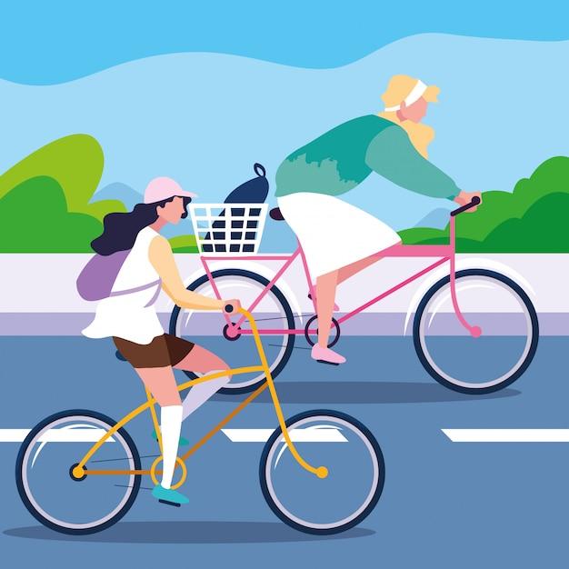 Mulheres jovens andando de bicicleta na estrada Vetor Premium