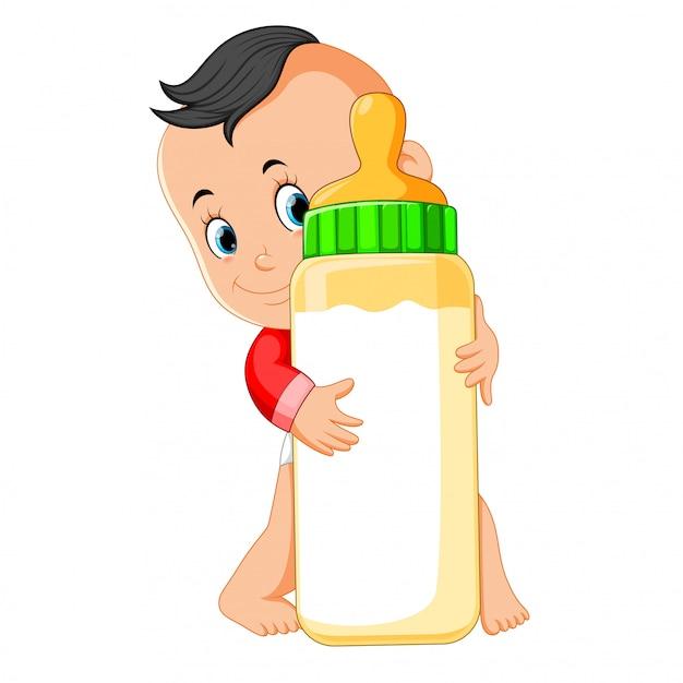 O bebê feliz jogando e abraçar a garrafa de leite Vetor Premium
