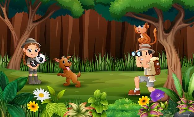 O explorador com animais na floresta Vetor Premium