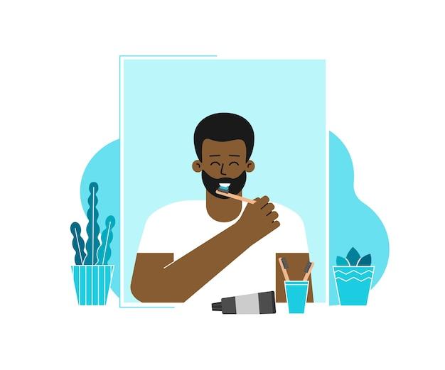 O homem está limpando os dentes com escovas de dentes, pasta. cara na frente do espelho, sorrindo Vetor Premium